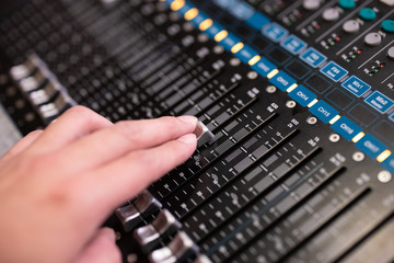 Hand using sound music mixer control panel in the event hall