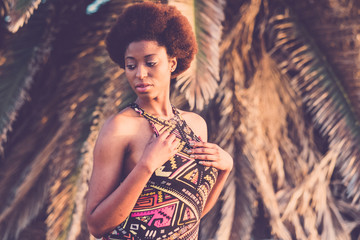 Black african beautiful young woman pose with athnic traditional dress and afro hairstyle with tropical palm in background - beauty concept for cute girl outdoor