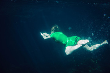 short-haired girl in a green dress swims underwater in the sea