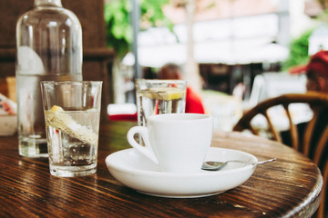 Closeup of a cup of coffee and some glasses on a wooden table in the morning with sunlight and relaxing in the free time. Photo of a moment of relax in the holiday with a hot beverage