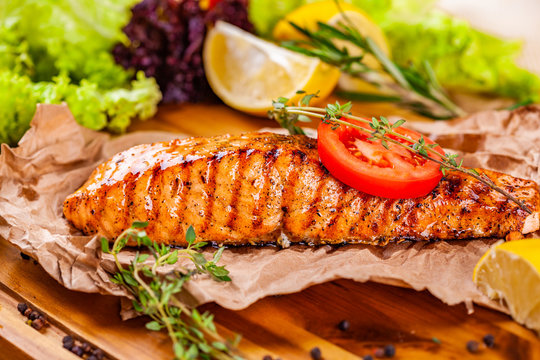 Grilled salmon with tomato and herbs on wooden board
