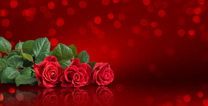 Card for Valentines Day or wedding with roses bouquet on red background with glowing bokeh