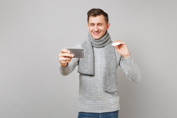 Smiling young man in gray sweater, scarf holding thermometer, doing selfie shot on mobile phone, making video call isolated on grey background. Health ill sick disease treatment, cold season concept.