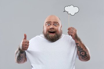 Excited man holding thought cloud and putting thumb up