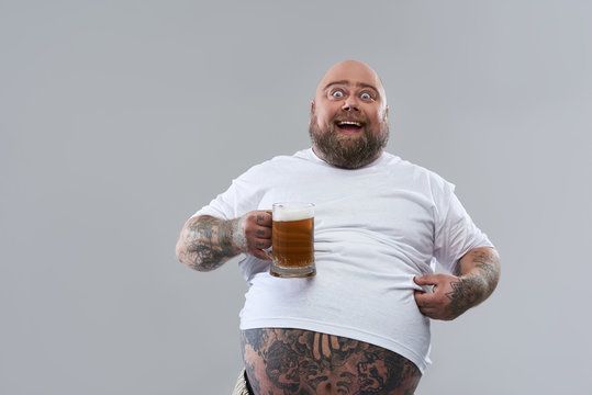 Excited fat man revealing his belly and holding beer