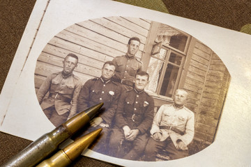 Photo card of five Latvian soldiers in period around 1935 and rifle bullets on trench coat at background