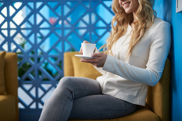 Young woman with long curly hair enjoying hot drink