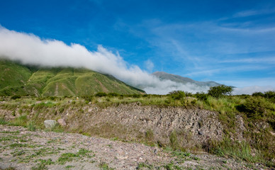 Landscape of green mountains with low clouds.
