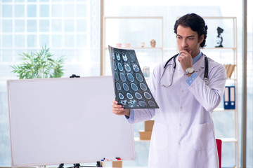 Young handsome male radiologist in front of whiteboard