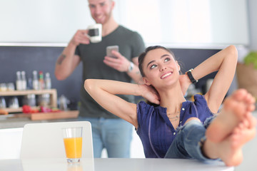 Happy couple using smartphone sitting in kitchen