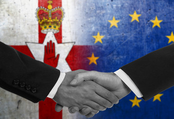 Two men/politicians in suits shaking hands with the national flags on the background - European Union and Northern Ireland