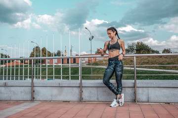 Girl athlete, summer city. Listening to music in headphones, resting after a morning run. In leggings sneakers. Woman with tattoos. In hands of a smartphone watching a video. Free space for text.