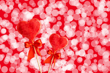 Two sweet hearts with bows on sticks with abstract background