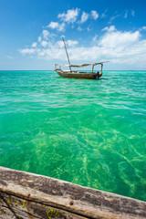 boat behind wooden board in emerald sea