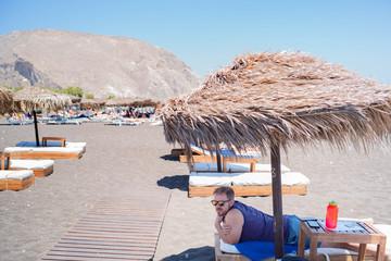 men sunbath on a beach