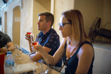 Friends try wine at a vineyard