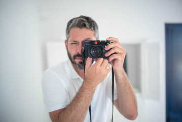 A man takes a selfie in the mirror with a vintage looking camera