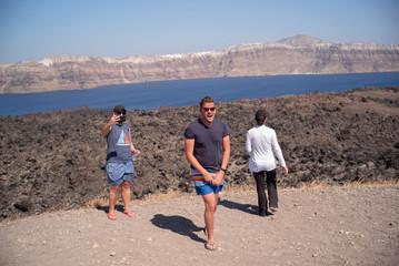 Friends hike on Nea Kameni, a small uninhabited Greek island of volcanic origin located in the Aegean Sea within the flooded Santorini caldera.