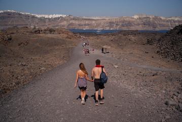 A couple hike together on Nea Kameni, a small uninhabited Greek island of volcanic origin located in the Aegean Sea within the flooded Santorini caldera.