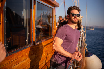 young man on a boat wearing sunglasses on a sunny day