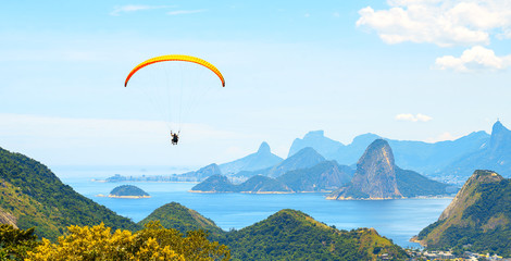 A colorful parachute with skydiver on sunny blue sky background. Active lifestyle. Extreme sport. Concept of holidays, vacation, tourism. horizontal. Aerial view of Rio de Janeiro with turquoise water Wall mural