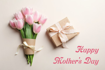 Beautiful tulips and gift box for Mother's Day on light background, top view
