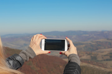 Woman taking photo of beautiful mountain landscape with smartphone