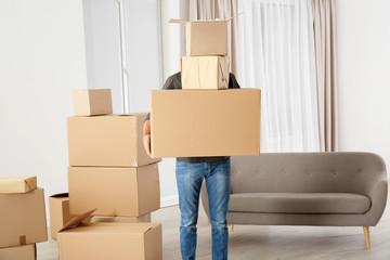 Man with moving boxes in his new house