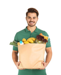 Young man holding paper bag with products on white background. Food delivery service