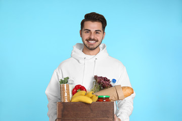 Young man holding wooden crate with products on color background. Food delivery service