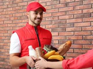 Male courier delivering food to client indoors