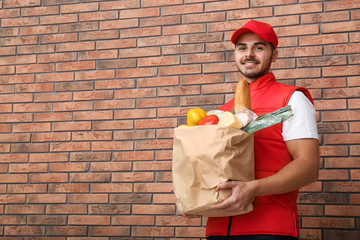 Food delivery courier holding paper bag with products near brick wall. Space for text