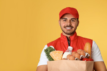 Food delivery courier holding paper bag with products on color background. Space for text
