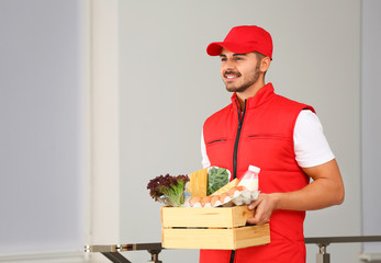 Food delivery courier holding wooden crate with products indoors. Space for text