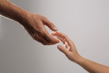 Man reaching for woman's hand on grey background, closeup. Help and support concept