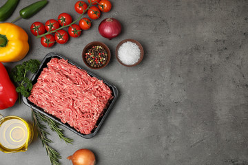 Flat lay composition with minced meat and space for text on grey background