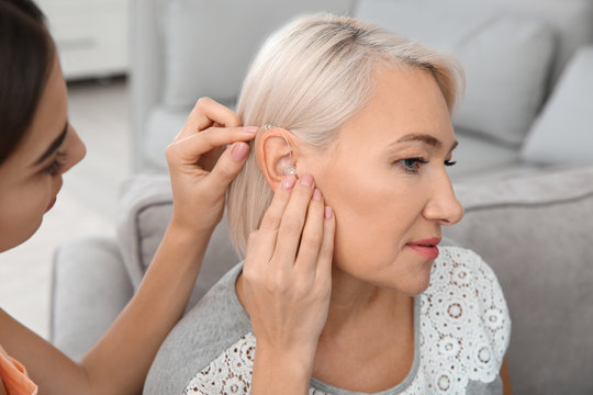 Young woman putting hearing aid in mother's ear indoors