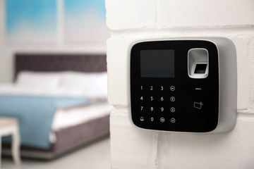Modern alarm system with fingerprint scanner on brick wall in house. Space for text