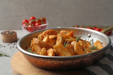 Baked potatoes with rosemary in frying pan on table