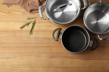 Flat lay composition with clean cookware and space for text on wooden background