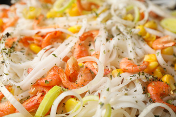 Rice noodles with shrimps and vegetables as background, closeup