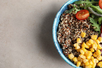 Healthy quinoa salad with vegetables in bowl on color background, top view. Space for text