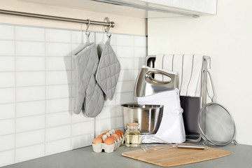 Set of clean cookware, utensils and eggs on table in modern kitchen