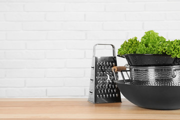 Set of clean cookware and lettuce on table against  white brick wall. Space for text
