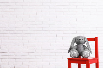 Stuffed toy rabbit on chair against white brick wall, space for text. Child room interior details
