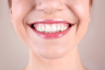 Young woman with healthy teeth smiling on color background, closeup
