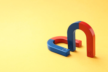 Red and blue horseshoe magnets on color background. Space for text