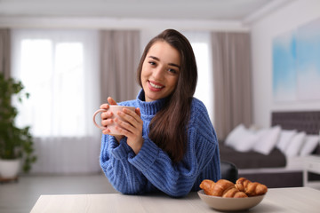 Young woman drinking coffee at table indoors. Winter season