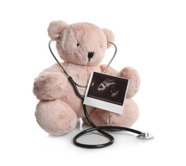 Ultrasound photo of baby and toy teddy bear on white background. Concept of pregnancy