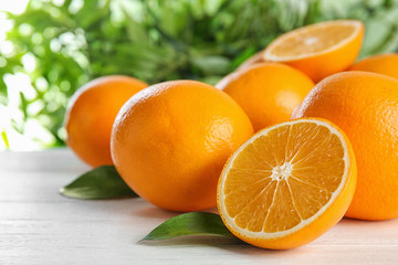 Fresh juicy oranges with leaves on wooden table